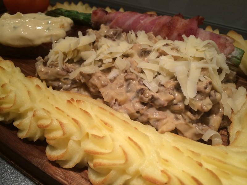 Montera ihop plankan och strö riven ost över köttet och sås.